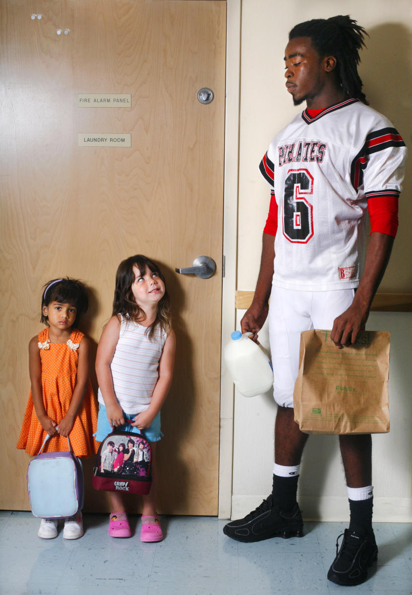 "The Pasco High School quarterback shares a look with a kindergartener during a ""back to school"" portrait session."