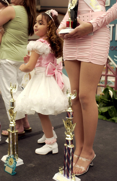 Kylee Buffardi, 5, left, stands next to her cousin, Naobi Lantigua, 15, after the two received their trophies in the Sweet Pea Pageant held in the Crystal River Mall.