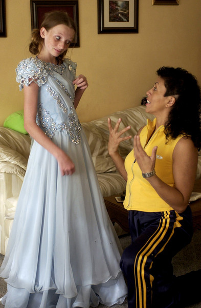 Molly Storts, 13, a pageant veteran who has been competing since the age of 9, skeptically looks at her longtime modeling coach, DiAna Carrasquillo, 42, as Carrasquillo makes suggestions on how to salvage Stort's damaged rhinestone-laden competition gown, which arrived just days before Storts was to compete in the 2005 Sweet Pea Pageants National Finals in Cocoa Beach.