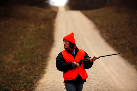 Monica Eng clutches her shot gun while listening for deer during her first hunting season in northern Illinois.