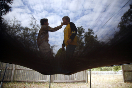 Ryan Moran, 12, reaches out for his twin brother Anthony while the two jump on the trampoline outside their house in Interlachen, Fla. Ryan is severely autistic and cannot sit still or avoid unintelligible outbursts.