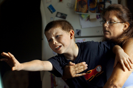Matthew Peck, 7, reaches away from his mother Cathy Peck as she tries to get him to finish his math lesson. Matthew, who has been diagnosed with Attention Deficit Hyperactivity Disorder, Dyslexia and exhibits anger and rage episodes, has trouble concentrating.