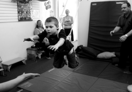 Jeffrey Leonbruno, right, watches Matthew perform a sensory integration exercise at Sensations Pediatrics Therapy.