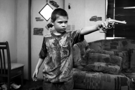 Matthew points a toy gun at his siblings.