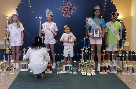 Carrasquillo's group stands with their trophies, crowns and plaques after competing in the 2005 Sweet Pea Pageants National Finals in Cocoa Beach.