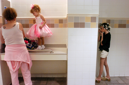 Linda Wilson, left, dresses her daughter, Diane, 4, while Storts applies her eye makeup in the bathroom of the Gulf View Square Mall before competing in the Little Miss-Mr. Octoberfest Pageant.