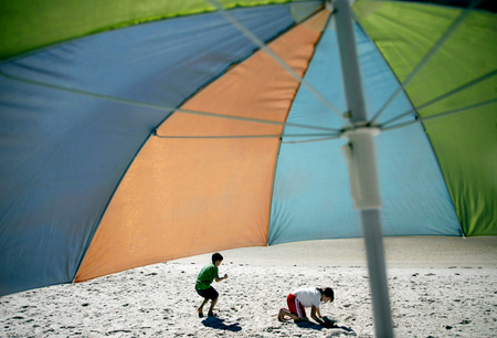 Brett McCarthy, 8, left, and his sister Brandy McCarthy, 10, play in the sand at Pine Island, Fla.