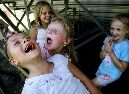 Marissa Hawk, 6, front left, laughs while Katie Hedges, 7, pretends to be an alien in a park in Spring Hill, Fla.