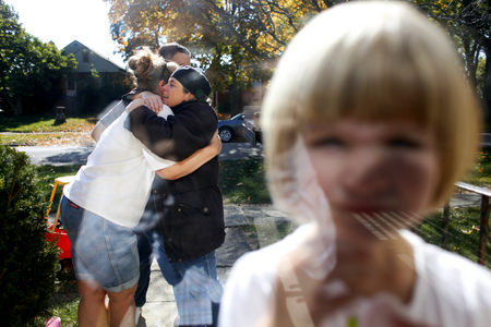 Beth Mackie, left, hugs friend Carol Bachelor as Mackie's daughter Lily, 3, stands in the doorway of the Mackie home on moving day in Wheaton, Ill. The family was forced to leave their home after it fell into foreclosure.