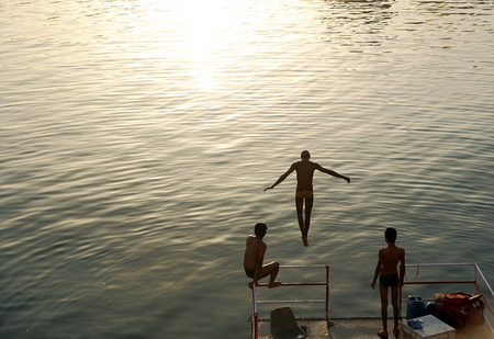 A group of young men take a swim in Lake Pichola as the sun sets in Udaipur in the state of Rajasthan in western India.