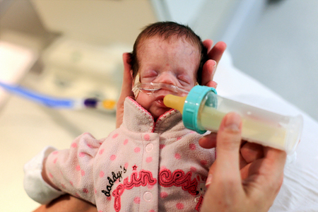 Jo Johnson, of McHenry, feeds her daughter Regina, 32 weeks, a bottle of donor breast milk in the NICU at Advocate Lutheran General Hospital in Park Ridge, Ill.